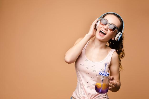 Jovem morena cantando e bebendo limonada saborosa