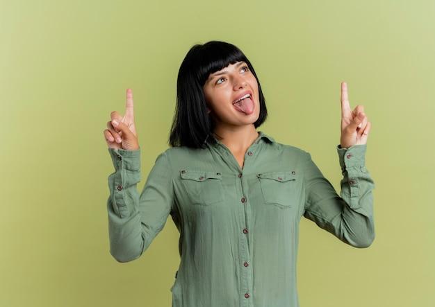 Jovem morena caucasiana alegre tira a língua e aponta para cima com as duas mãos isoladas em fundo verde oliva com espaço de cópia