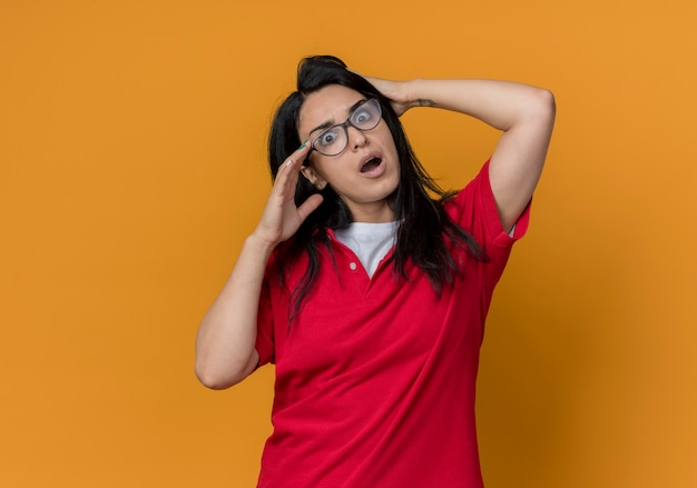 Jovem morena caucasiana chocada com óculos óticos e camisa vermelha segurando a cabeça parecendo isolada na parede laranja
