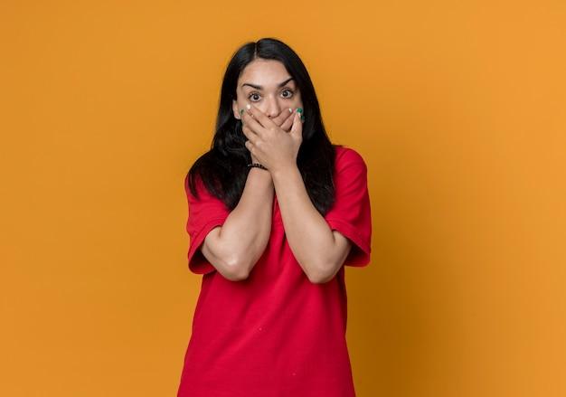 Jovem morena caucasiana chocada, vestindo uma camisa vermelha, segurando a boca com as duas mãos isoladas na parede laranja