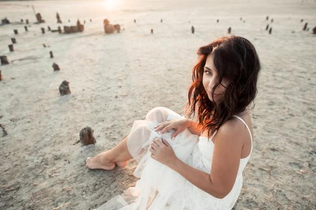 Jovem morena caucasiana está sentado na areia, vestida de vestido branco e olhando em linha reta