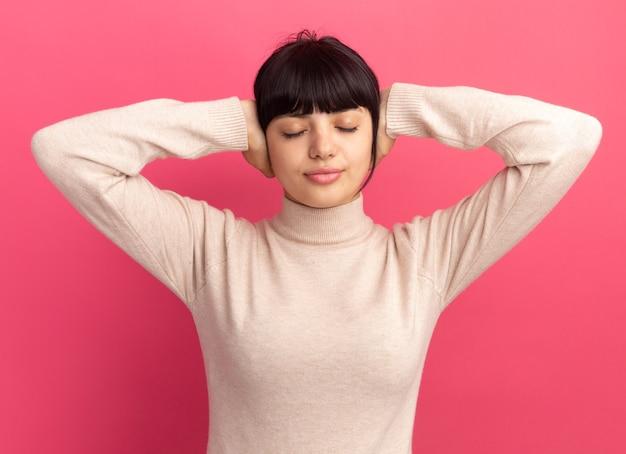 Jovem morena caucasiana satisfeita colocando as mãos nas orelhas em pé com os olhos fechados