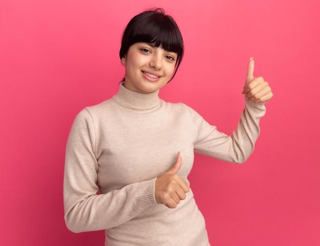 Jovem morena caucasiana satisfeita com o polegar para cima com as duas mãos
