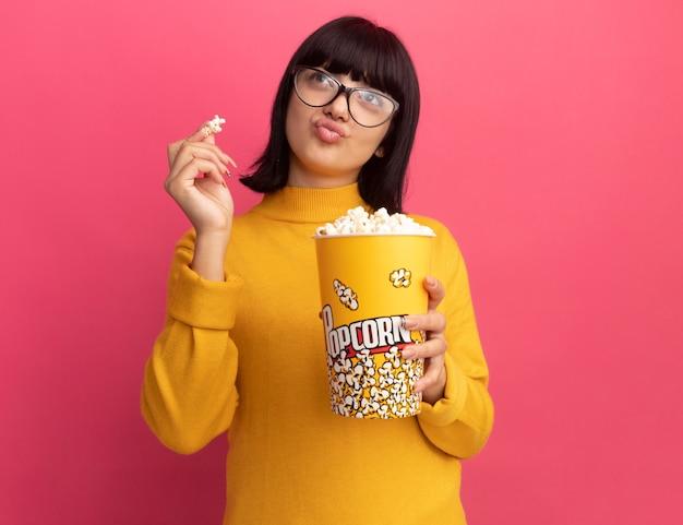 Jovem morena caucasiana satisfeita com óculos ópticos segurando um balde de pipoca e olhando para o lado