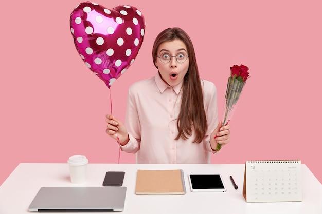 Jovem morena caucasiana segurando um balão em forma de coração e um buquê de rosas vermelhas