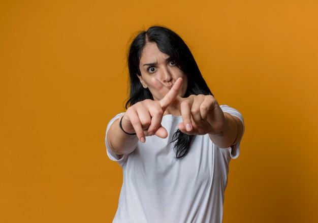 Jovem morena caucasiana séria cruzando os dedos gesticulando para nenhuma placa isolada na parede laranja