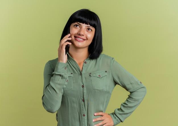 Jovem morena caucasiana sorridente coloca a mão na cintura falando no telefone, olhando para cima