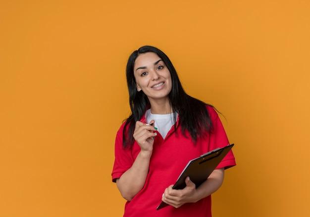 Jovem morena caucasiana sorridente de camisa vermelha segurando uma caneta e uma prancheta isoladas na parede laranja