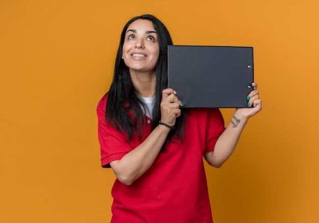 Jovem morena caucasiana sorridente de camisa vermelha segurando uma prancheta, olhando para cima isolada na parede laranja