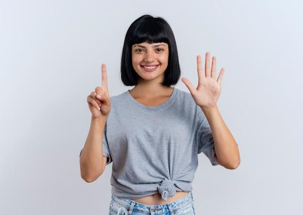 Jovem morena caucasiana sorridente gesticula seis com os dedos olhando