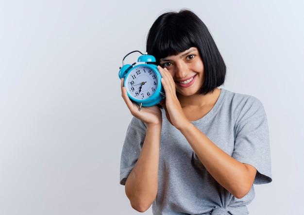 Jovem morena caucasiana sorridente segurando um despertador olhando
