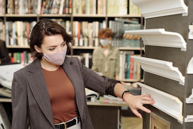 Jovem morena cliente do estúdio de design de interiores com máscara protetora examinando novas amostras de pedestais de plástico branco na loja
