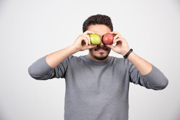 Jovem morena cobrindo os olhos com maçãs.