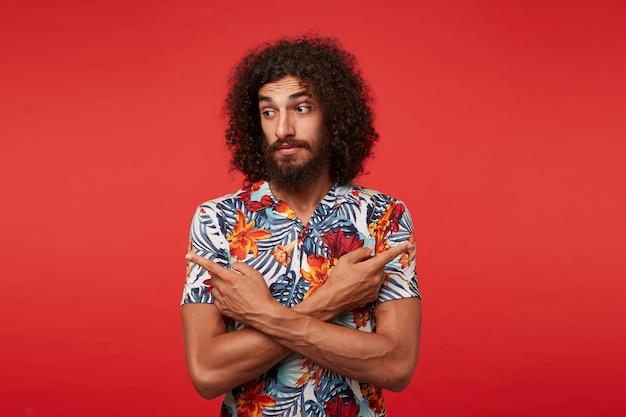 Jovem morena com barba encaracolada perplexa em uma camisa multicolorida com estampa floral enrugada na testa e olhando confusa para o lado, cruzando as mãos com os indicadores aparecendo em lados diferentes