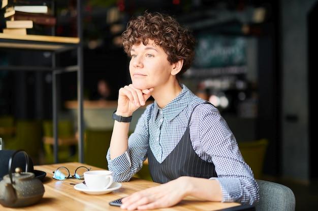 Jovem morena com cabelos cacheados, sentado no café acolhedor e se inspirar na xícara de chá