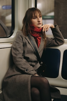 Jovem morena com casaco no carro do metrô olhando pela janela