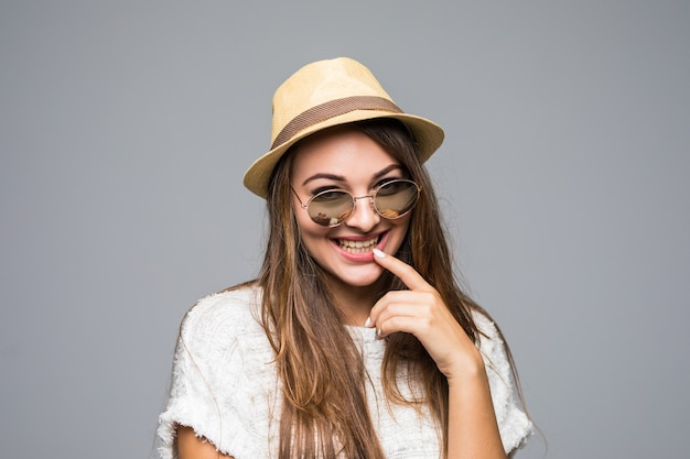Jovem morena com chapéu e óculos escuros sorrindo em cinza