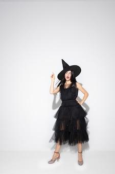 Jovem morena com chapéu preto e fantasia em fundo branco. modelo feminino caucasiano atraente. halloween, sexta-feira negra, cyber segunda-feira, vendas, conceito de outono. copyspace. apontando, posando.