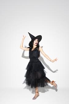 Jovem morena com chapéu preto e fantasia em fundo branco. modelo feminino caucasiano atraente. halloween, sexta-feira negra, cyber segunda-feira, vendas, conceito de outono. copyspace. dançando, posando.