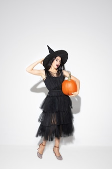 Jovem morena com chapéu preto e fantasia em fundo branco. modelo feminino caucasiano atraente. halloween, sexta-feira negra, cyber segunda-feira, vendas, conceito de outono. copyspace. detém bombeamento.