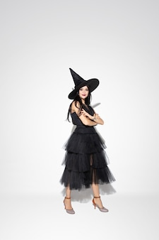 Jovem morena com chapéu preto e fantasia em fundo branco. modelo feminino caucasiano atraente. halloween, sexta-feira negra, cyber segunda-feira, vendas, conceito de outono. copyspace. mãos cruzadas em pé.