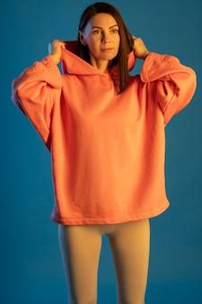 Jovem morena com legging esportiva e top laranja com capuz na superfície azul