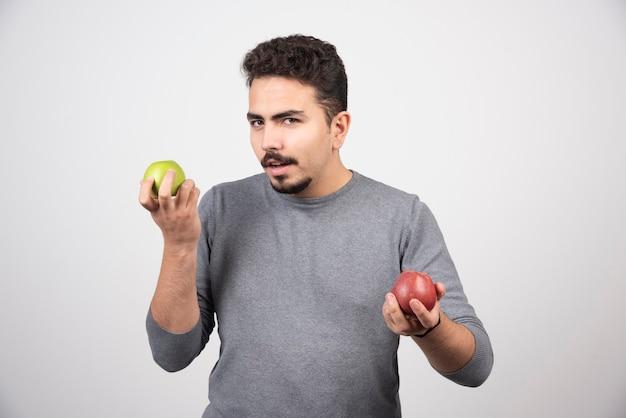 Jovem morena com maçãs posando em cinza.