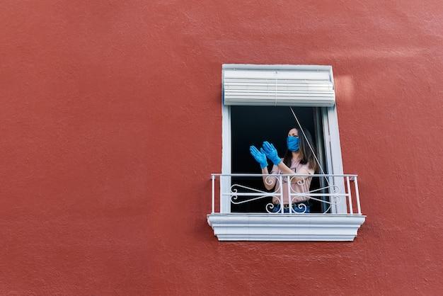 Jovem morena com máscara batendo palmas da janela da casa