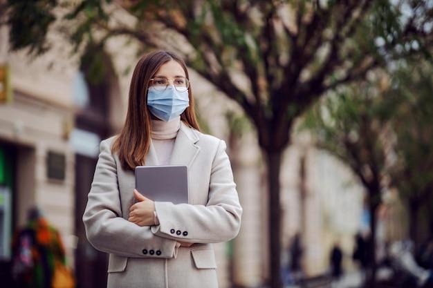 Jovem morena com máscara facial em pé na rua segurando o tablet