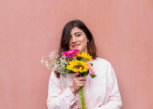 Jovem morena com monte de flores desabrochando