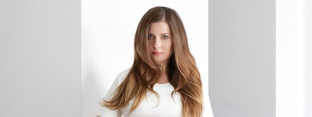 Jovem morena com penteado longo ondulado no interior branco, cuidados com os cabelos e conceito de beleza de luxo