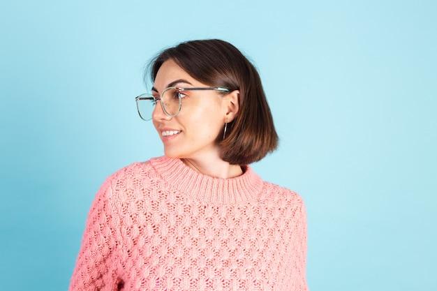 Jovem morena com suéter rosa isolada na parede azul