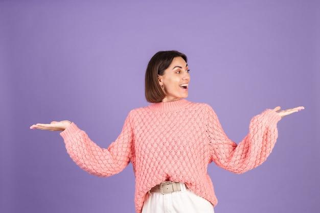 Jovem morena com suéter rosa isolada na parede roxa