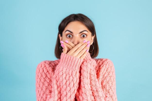 Jovem morena com suéter rosa quente isolada na parede azul