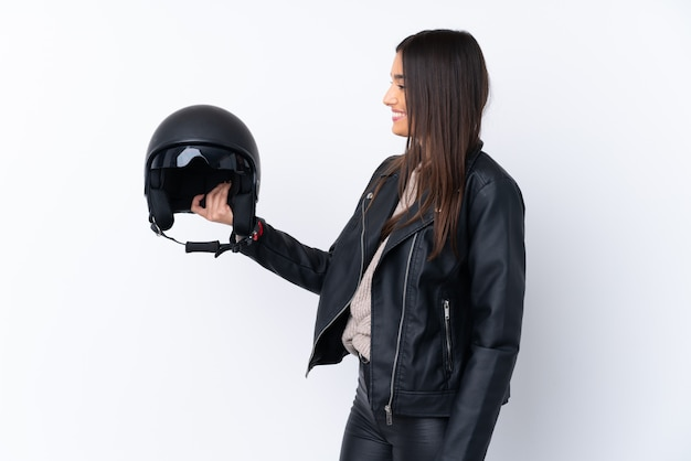 Jovem morena com um capacete de moto sobre parede branca isolada com expressão feliz