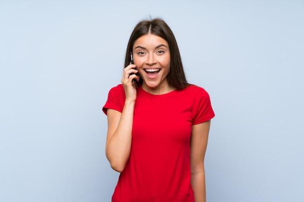 Jovem morena com um telefone móvel isolado parede azul