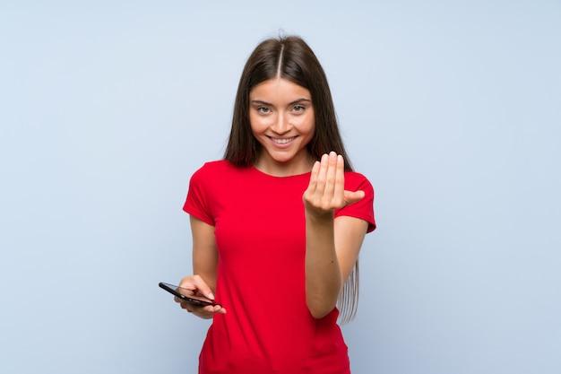 Jovem morena com um telefone móvel sobre parede azul isolada, convidando para vir com a mão.
