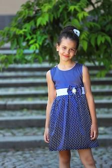 Jovem morena com um vestido azul no parque no verão. foto de alta qualidade