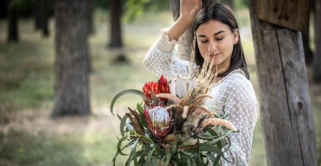 Jovem morena com um vestido branco com um buquê de flores na floresta em um fundo desfocado, copie o espaço.