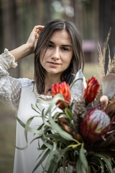 Jovem morena com um vestido branco com um buquê de flores na floresta em um fundo desfocado.