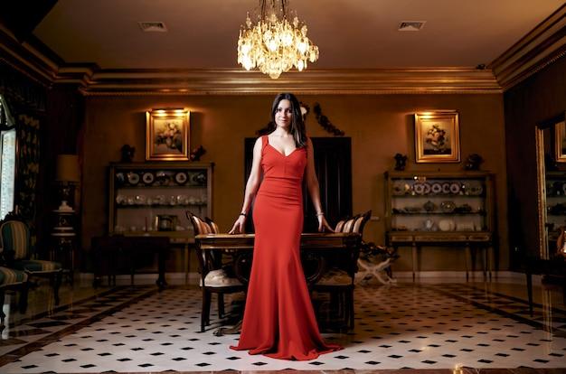 Jovem morena com um vestido vermelho na sala de estar