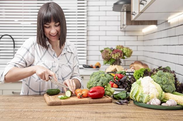 Jovem morena corta legumes na salada no espaço interior da cozinha moderna.