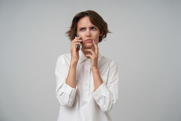 Jovem morena de aparência séria com corte de cabelo curto, segurando um telefone celular e conversando com os parceiros, sobrancelhas franzidas pensativamente, isolada