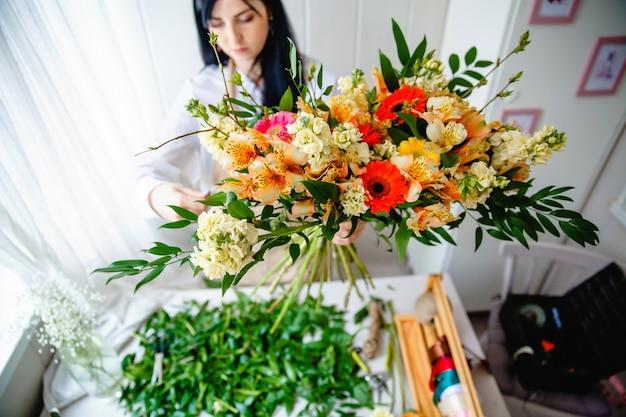 Jovem morena de avental no processo de criação de um buquê em estilo rústico em sua floricultura