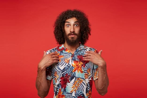 Jovem morena de barba encaracolada espantada se mostrando com as palmas das mãos levantadas e olhando para a câmera com os olhos arregalados, vestido com uma camisa multicolorida florida em pé sobre um fundo vermelho