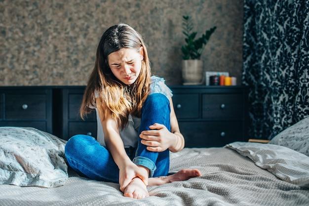 Jovem morena de blusa branca e jeans azul sentada em uma cama no quarto, segurando uma perna dolorida