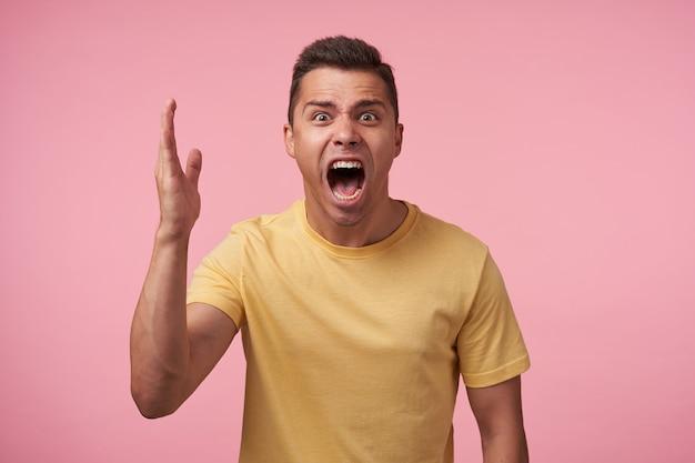 Jovem morena de cabelo curto irritado com corte de cabelo curto gritando mal-humorado com a boca bem aberta e levantando a palma da mão emocionalmente enquanto posava sobre um fundo rosa