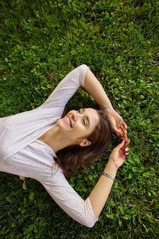 Jovem morena de cabelos compridos satisfeita em roupas elegantes, relaxando no gramado verde em um dia quente de primavera, mantendo as mãos levantadas e sorrindo agradavelmente enquanto olha para o lado