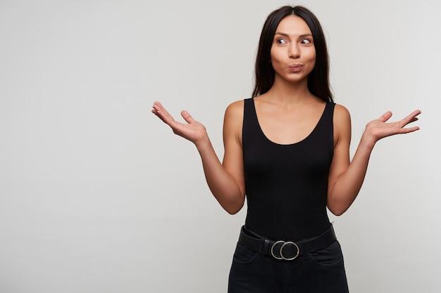 Jovem morena de cabelos compridos surpresa feminina olhos arredondados enquanto olha positivamente para o lado e levantando as palmas das mãos, vestida com roupas pretas casuais enquanto posa em branco