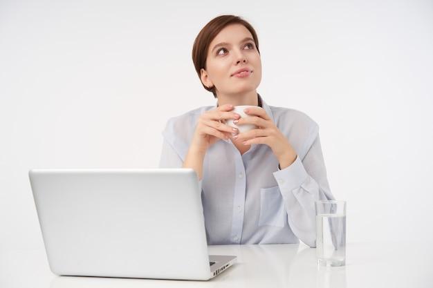 Jovem morena de cabelos curtos de aparência agradável com penteado casual sorrindo positivamente enquanto pensa em algo positivo e bebendo uma xícara de café, isolada no escritório branco